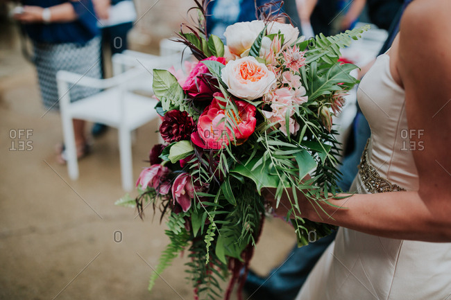 Side view of bride holding fresh flower bouquet