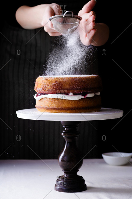 Female hands frosting a cake with powdered sugar