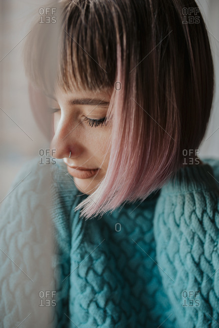 Woman in a comfortable sweater closes her eyes