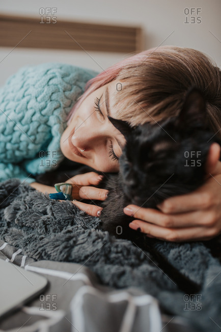 Woman cuddles with her cat