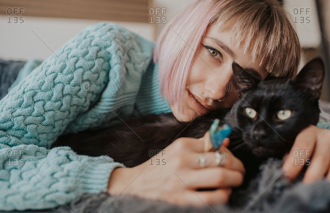 Woman lies down with her arms around her cat