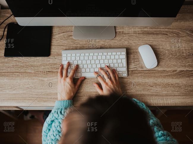 Woman types on her desktop computer