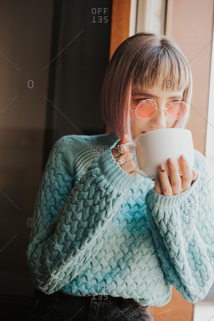 Fashionable woman looks out the window while drinking coffee
