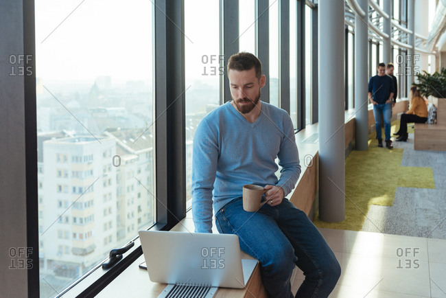 Man drinking tea and working on his computer at the company