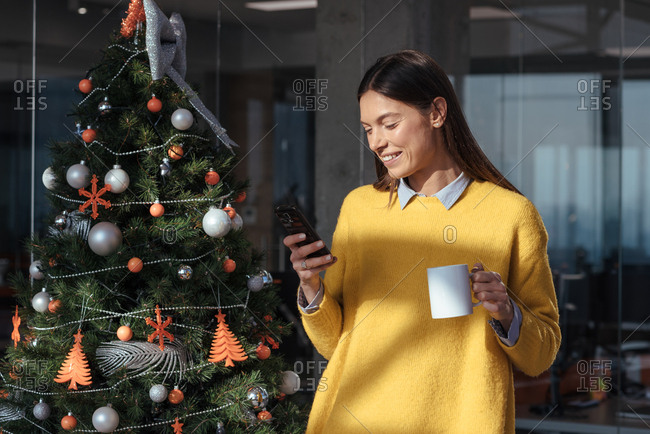Young woman at work holding her phone