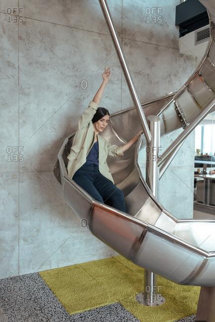 Woman in a office slide having fun