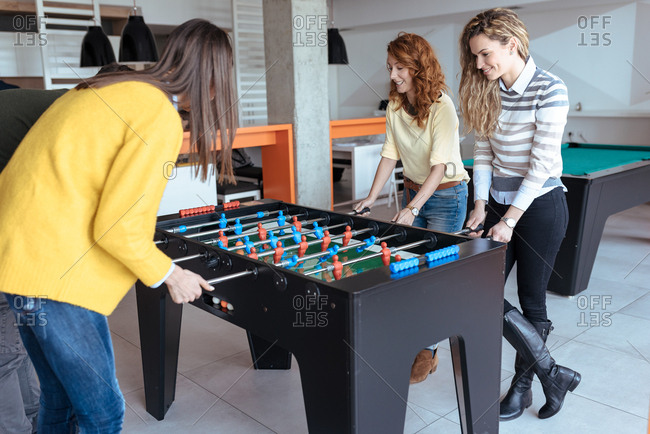 Colleagues playing table football at work