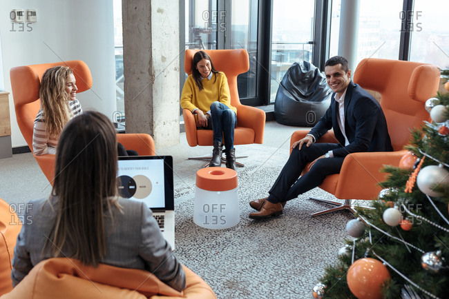 Colleagues spending time at relaxing area at work talking to eachother