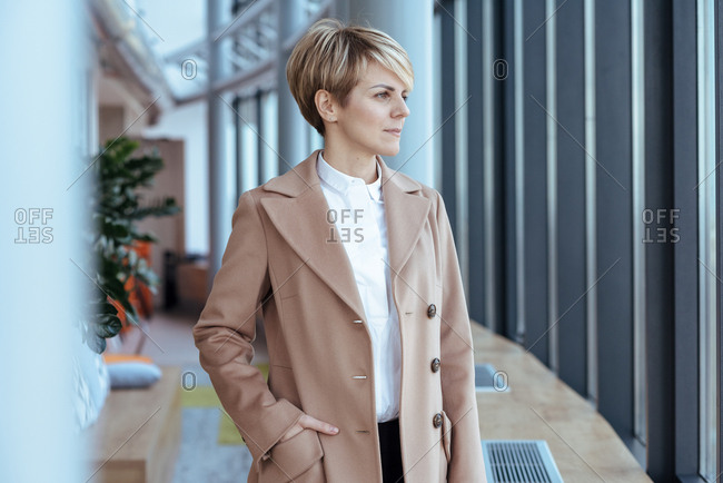 Woman in beige coat at the office