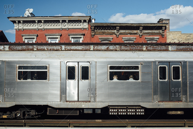 Silver subway car against buildings
