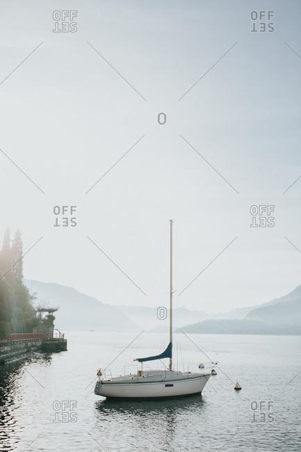 Solo sailing boat on the coast of Lake Como, Italy.