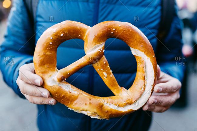 Man holding a giant pretzel.