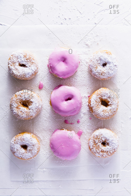 nine pink and sugared donuts shot overhead