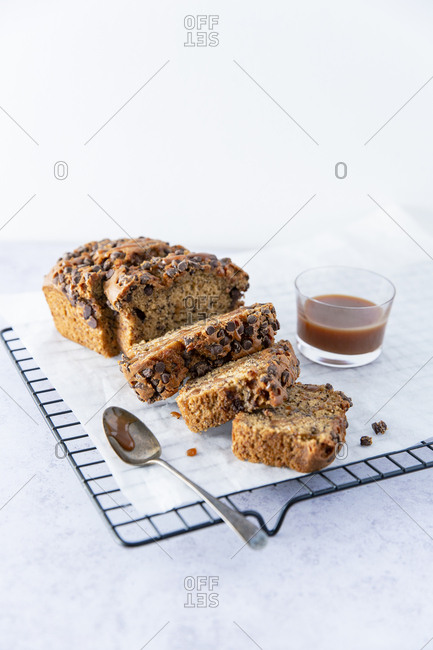 chocolate chip banana bread on a baking rack with caramel sauce