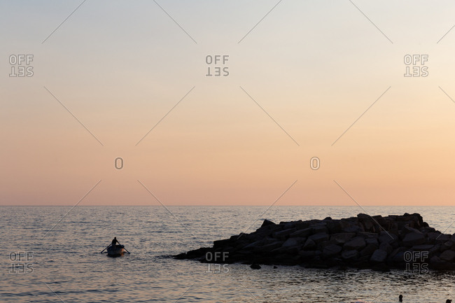 A man rowing a small manual boat out of a small fishing harbor in the South of Italy.