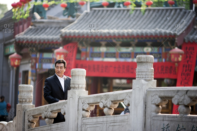 Portrait of businessman standing in front of a traditional Chinese building.