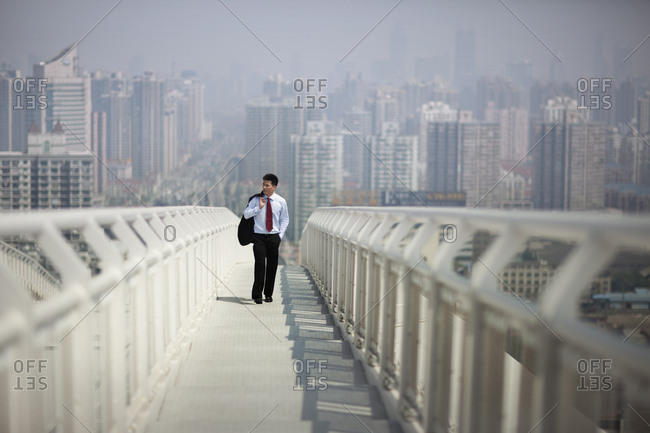 Young businessman walking along a footbridge in the city.