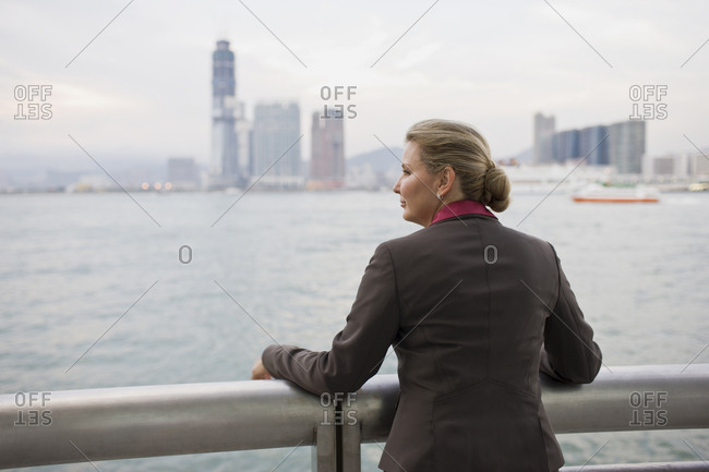 Mid-adult businesswoman standing at a railing overlooking a city harbor.
