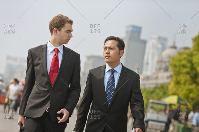 Business colleagues walking and talking.