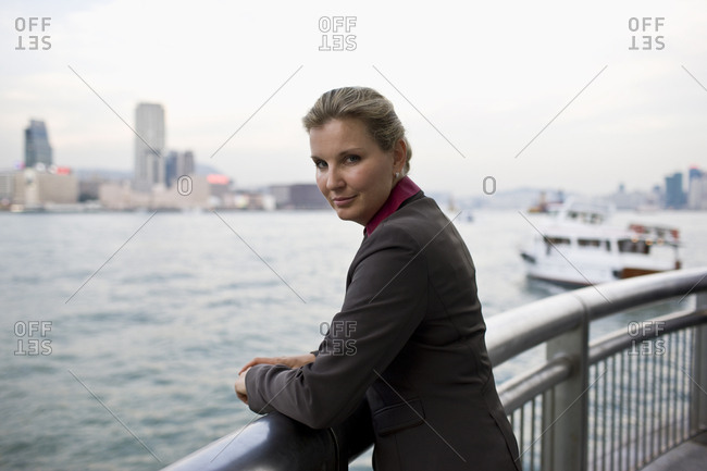 Portrait of a mid-adult businesswoman standing at a railing overlooking a city harbor.