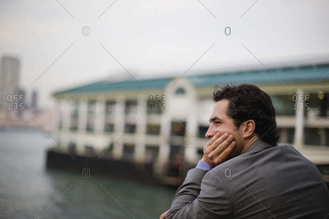 Serious young businessman looking out over a harbour with his hand on his chin in the city.