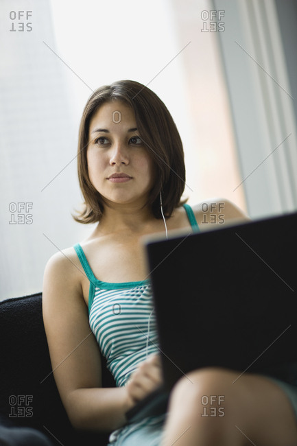 Teenage girl sitting with a laptop with earphones in.