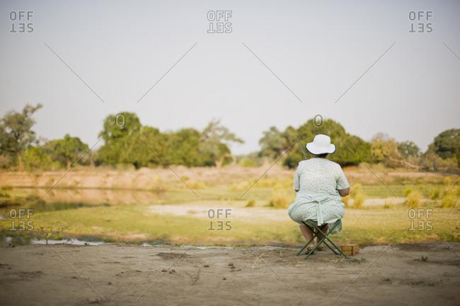 Mature woman sitting fishing by a lake.