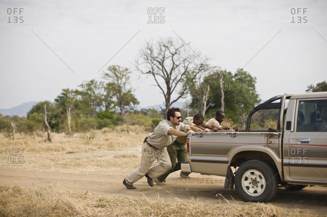 Three mid-adult men pushing a truck along a dirt road.