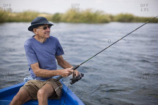 Senior man sitting in a boat fishing.