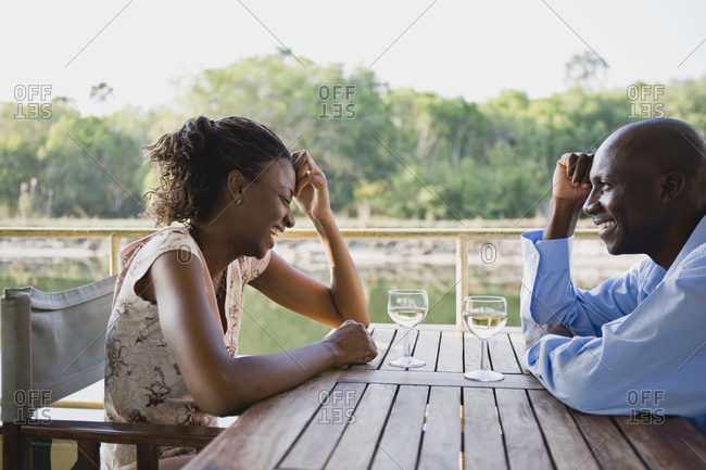Happy mid-adult couple seated at an outdoor table.