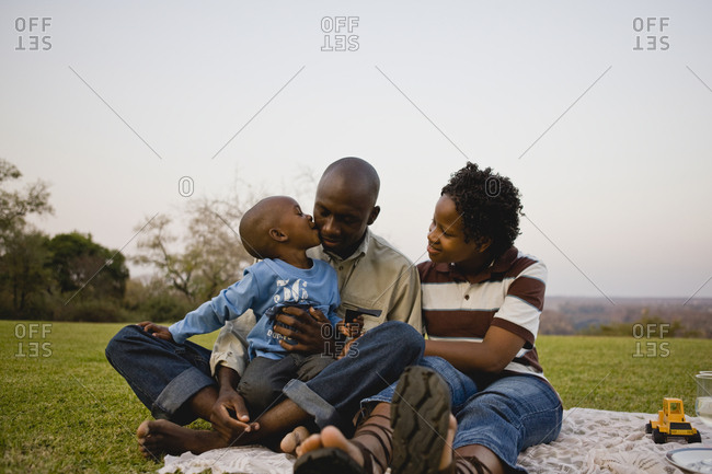 Young boy having a picnic with his young adult mother and father.