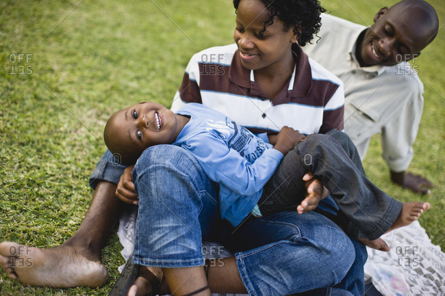 Portrait of a young boy having a picnic with his young adult mother and father.