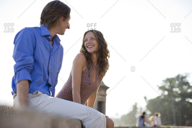 Mid-adult couple sitting on a stone wall looking at each other.