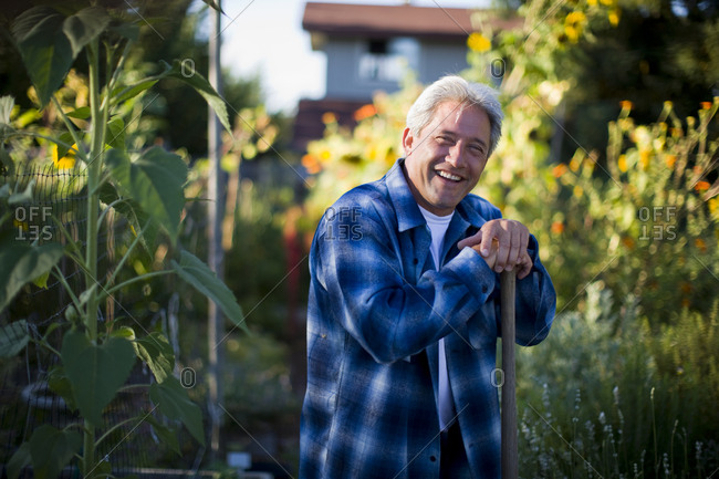 Portrait of a happy mature man leaning on the handle of a spade in his garden