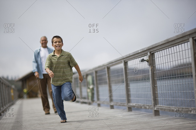 Happy young boy running down a wharf followed by his father.