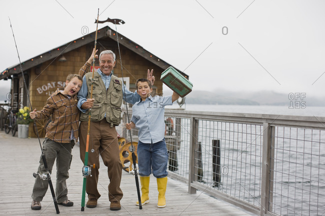 Portrait of a happy father making silly faces with his two sons on a wharf while holding fishing gear.