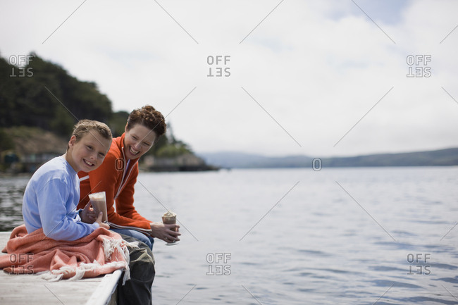 Portrait of a smiling boy sitting with his mother on the edge of a jetty holding a chocolate drink.