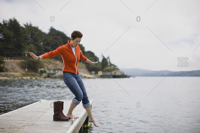 Mid-adult woman testing the water with a bare foot off the edge of a jetty.