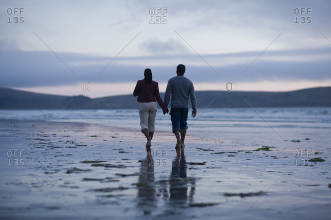 Mid adult couple holding hands and walking along a remote beach at sunset.