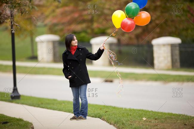 Teenage girl holding bunch of balloons
