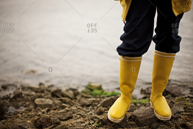 Person in gumboots standing on rocky shore
