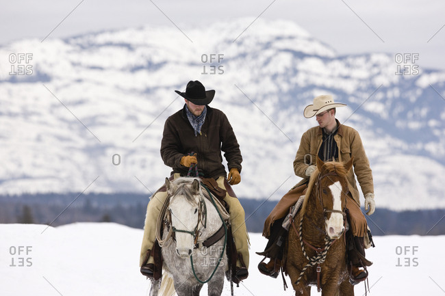 Two cowboys riding horses in a snow-covered countryside.