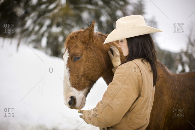 Young woman patting horse in the snow