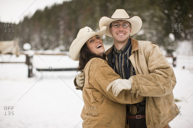 Young couple wearing cowboy hats on a snowy farm