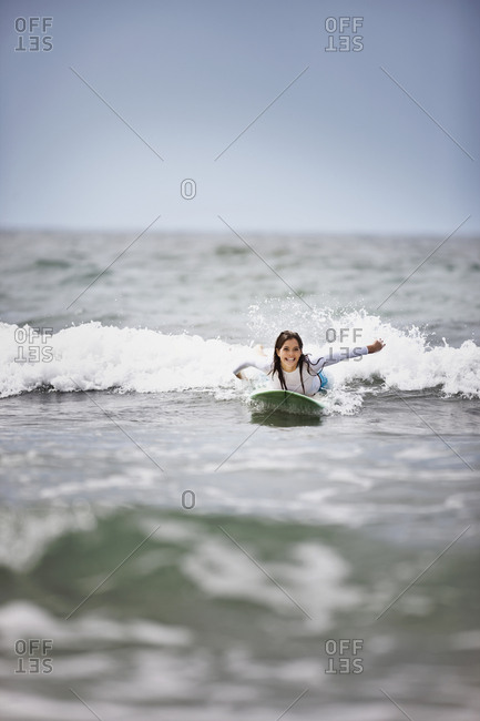 Young woman surfing at the beach.