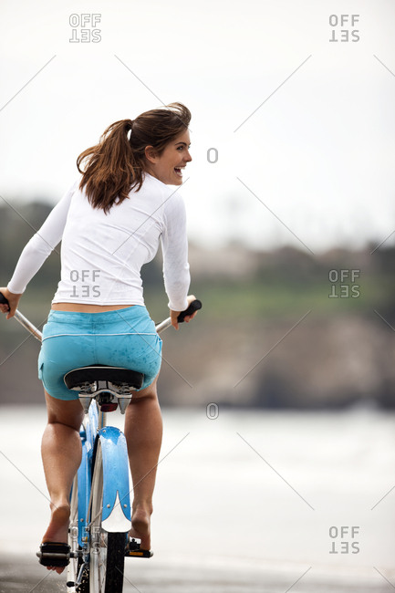 Young woman riding her bike on the beach.