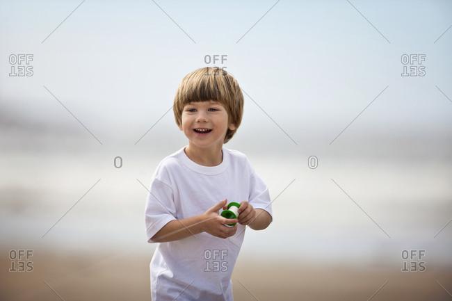 Portrait of preschool age boy flying a kite  at the beach.