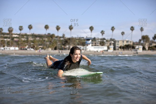 Young woman heading into the surf on a surfboard.