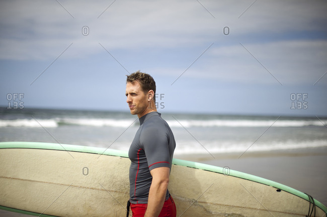 Portrait of man on the beach with his surfboard.