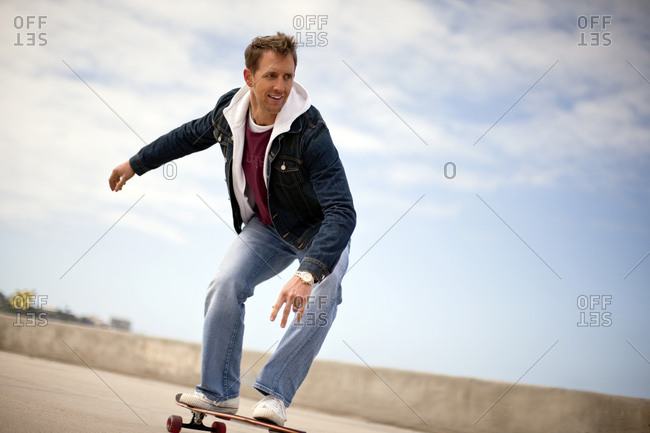 Young man skateboarding along the coast.